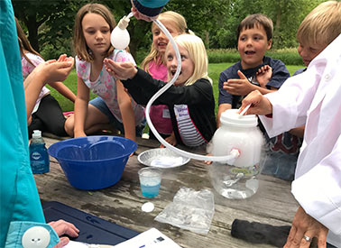 Adults working with kids on science experiments
